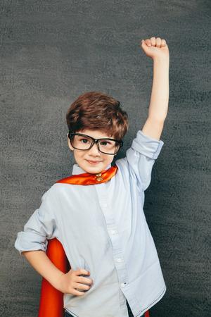 칠판에 대한 명랑 웃는 어린 아이 (소년) 그의 손을 올렸다. 학교와 슈퍼 히어로 개념