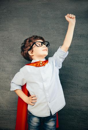 칠판에 명랑 웃는 어린 아이 (소년) 그의 손을 올렸다. 학교와 슈퍼 히어로의 개념 스톡 콘텐츠