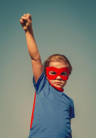 재미 있은 작은 전원 슈퍼 영웅 자식 (여자) 빨간색 우비에. 슈퍼 히어로 개념입니다. Instagram 색상 토닝 스톡 콘텐츠