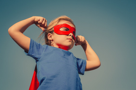 面白いパワーのスーパー ヒーローで小さな子供 (女の子) 赤レインコート。スーパー ヒーローのコンセプトです。Instagram の色の調子を整える 写真素材