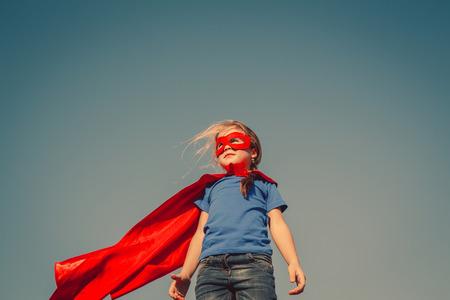 Grappig weinig stroom super held kind (meisje) in een rode regenjas. Superhero concept. Instagram kleuren toning Stockfoto