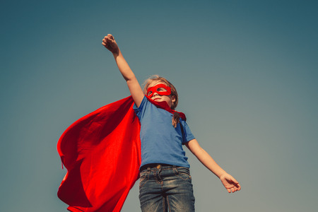 superhero: Funny little power super hero child (girl) in a red raincoat. Superhero concept. Instagram colors toning Stock Photo