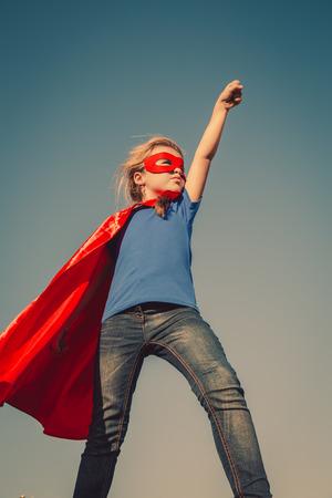 빨간색 우비에 재미있는 작은 전원 슈퍼 영웅 아이 (소녀). 슈퍼 히어로의 개념. 토닝 인스 타 그램 색상 스톡 콘텐츠