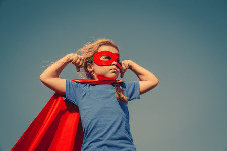 Funny little power super hero child (girl) in a red raincoat. Superhero concept. Instagram colors toning Archivio Fotografico