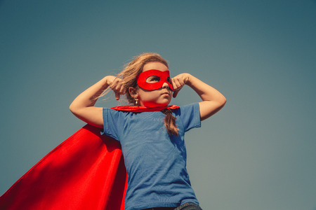 heroes: Funny little power super hero child (girl) in a red raincoat. Superhero concept. Instagram colors toning Stock Photo