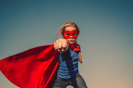 Funny little power super hero child (girl) in a red raincoat. Superhero concept. Instagram colors toning Archivio Fotografico