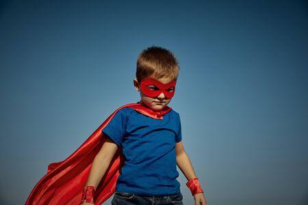 Lustiges kleines Power-Superheldenkind (Junge) in einem roten Regenmantel. Superhelden-Konzept
