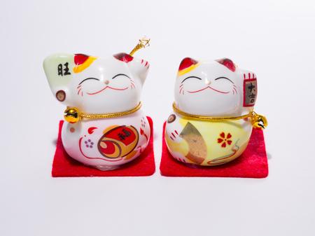 maneki neko: Welcoming the Japanese lucky cat. The Maneki Neko. The symbol means good luck or fortune. Isolated on white background Stock Photo