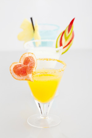 three cocktails with fruits on white background photo