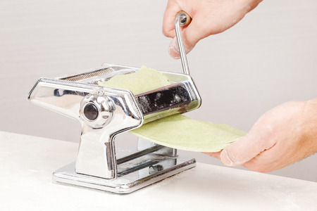 hand crank: the process of making noodles using pasta maker closeup on a white background Stock Photo
