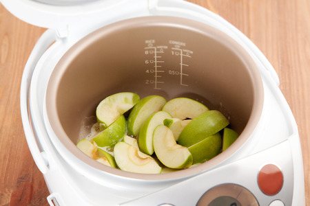 slow cooker: cooking pie with fresh apples in Multicooker closeup