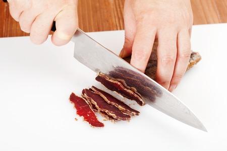het proces van het snijden van de gedroogd rundvlees op snijplank close-up Stockfoto