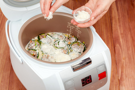 cooking zucchini rolls with cream sauce and cheese in multicooker closeup
