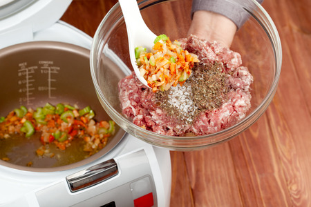 cooking ground meat with roasted vegetables in multicooker closeup