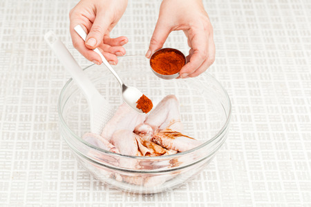 cook prepares chicken wings with spices in a glass bowl closeup