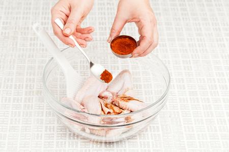 kok bereidt kippenvleugels met kruiden in een glazen kom close-up Stockfoto