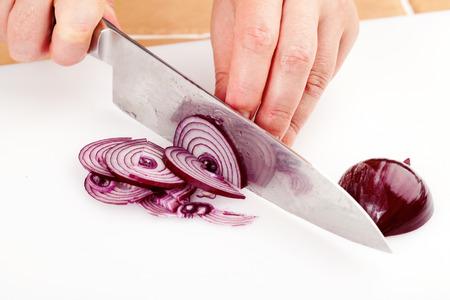 Chef-kok gehakt rode uien op een snijplank close-up
