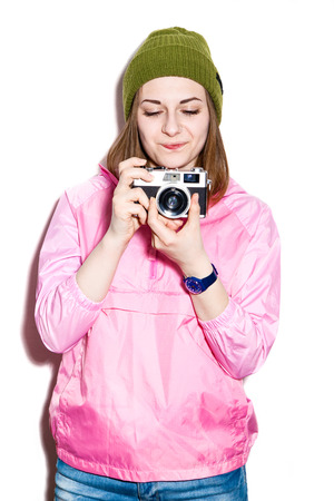 eyes downcast: Attractive young hipster girl with downcast eyes in a pink jacket and green hat. Cheerful girl with a camera. White background not isolated Stock Photo