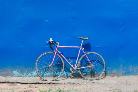 pink bike: Old hipster bike stands in the blue wall outdoors in summer day. Road bikes standing on a blue wall background brutal