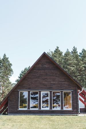 De gevel van een houten huis in het bos in de bergen. Houten huis in een Scandinavische stijl Stockfoto