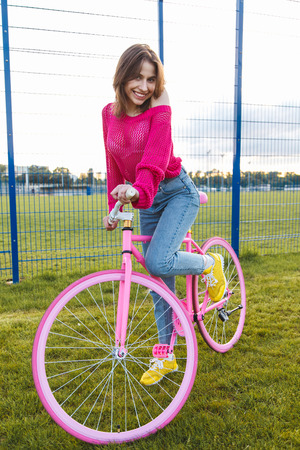 road cycling: Portrait of a young smiling woman with a trendy city bicycle on the stadium