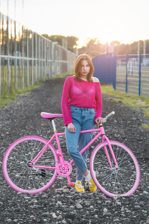 road cycling: Sexy girl standing next to a trendy bike outdoors during sunset. Soft light Stock Photo
