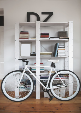 interiors design: Trendy bicycle in a modern interior. Hipster bike in the interior. Road bike near the bookshelves Stock Photo