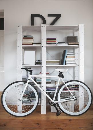Trendy fiets in een modern interieur. Hipster fiets in het interieur. Racefiets in de buurt van de boekenplanken Stockfoto