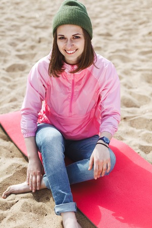 karemat: Young sexy hipster girl smiling sitting on a sandy beach