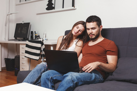 Young smilied couple with a laptop sitting on sofa at their home