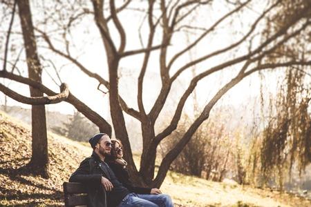 jonge mooie stijlvolle paar zittend op een bankje in de herfst park