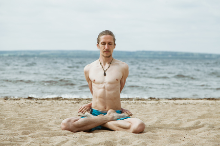 nude yoga: Adult male meditate, practice yoga outdoors on the beach