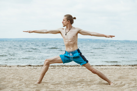 nude yoga: Adult thin man with naked torso doing yoga on the beach