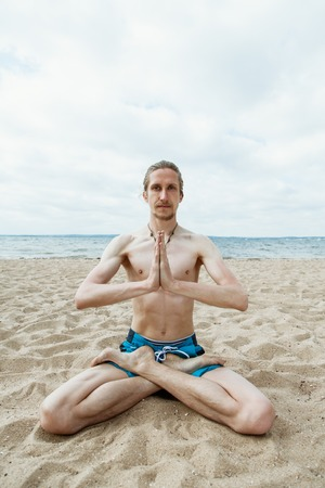 nude outdoors: Adult man leads a healthy lifestyle, doing yoga on the beach