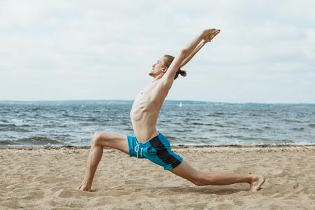 nude young: Взрослый худой человек с голым торсом занимаясь йогой на пляже. Virabhadrasana позе