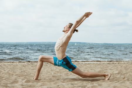 nude outdoors: Adult thin man with naked torso doing yoga on the beach. Virabhadrasana pose