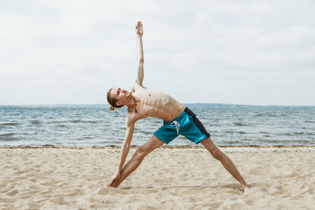 nude outdoors: Adult thin man with naked torso doing yoga on the beach. Utthita trikonasana pose Stock Photo