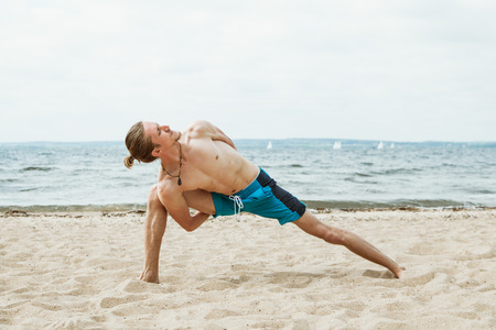 nude outdoors: Adult thin man with naked torso doing yoga on the beach. Parivritta parshvakonasana pose