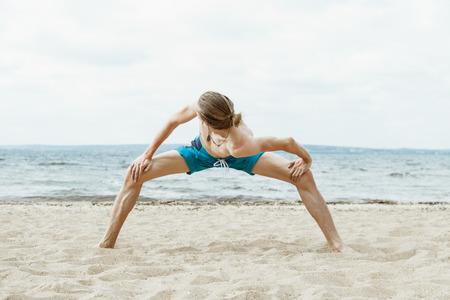 nude young: Молодой худой человек с голым торсом занимаясь йогой на пляже Фото со стока