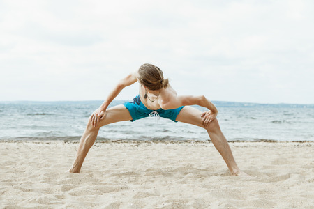 nude outdoors: Young thin man with naked torso doing yoga on the beach