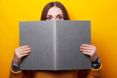 Young girl covers her face in fright on book a yellow background Stock Photo
