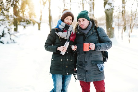 forest tea: Beautiful couple drinking tea in the winter forest. Rest in the winter forest