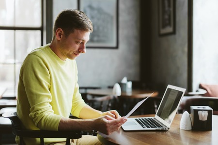 Jonge mannelijke blogger schrijft een nieuw artikel op uw blog zittend aan een tafel in de gezellige bar