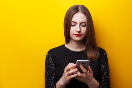 dependence: Beautiful female user mobile phones on a yellow background. Dependence on smartphone Stock Photo