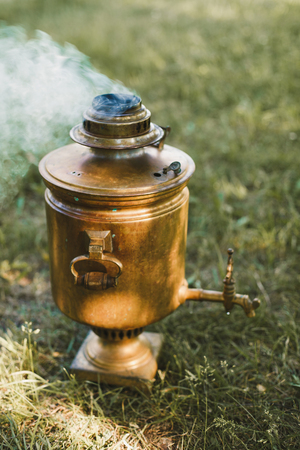 traditionally russian: Russian samovar on the wood stands on grass outdoors. Tea party outdoors