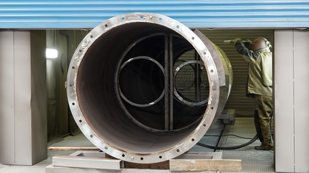 Arbeiter in einem Schutzanzug schützt das Metall Produkt mit Hilfe der Metallverarbeitung in der Fabrik von Strahl