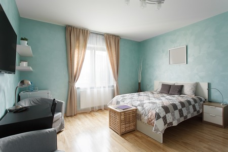 Spacious bedroom in blue color with a double bed. Interior design