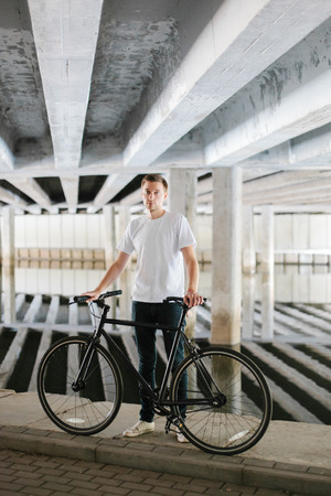 Young attractive man with a fashionable bicycle under a bridge Stock Photo