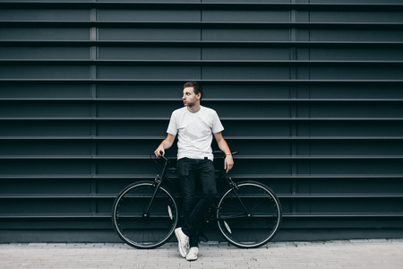 Adult hipster man with a fixed gear bicycle near the trendy colored wall