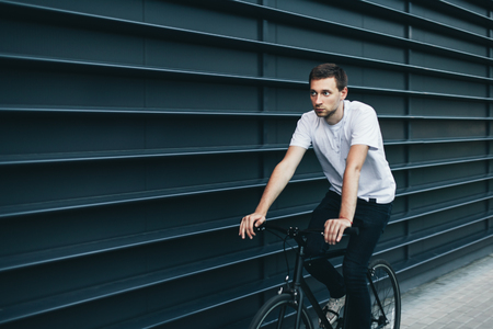 Young hipster man ride a fixie bicycle near the trendy colored wall